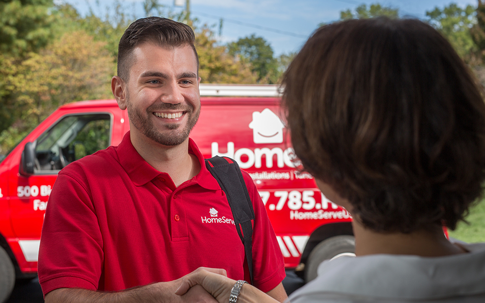 two people shaking hands in front of a Homeserve van